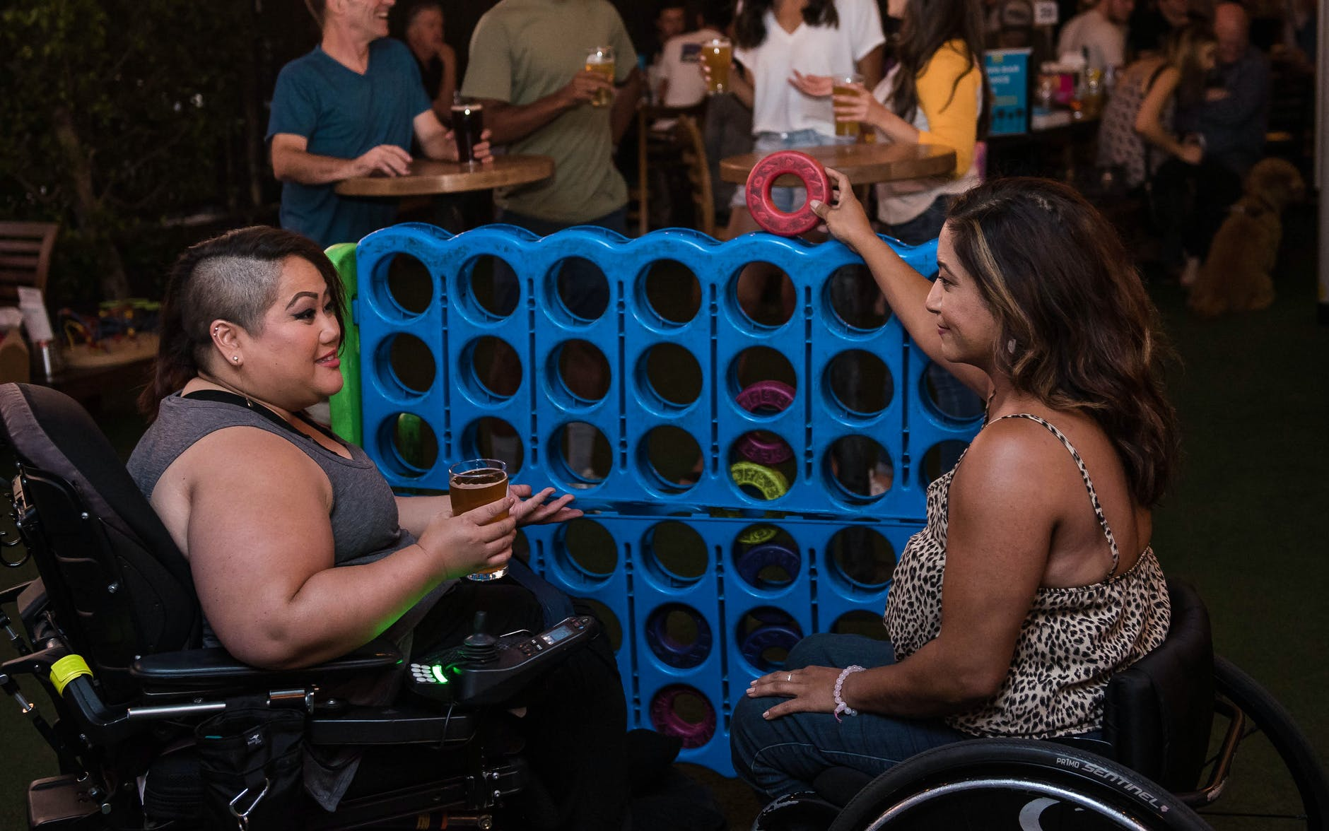 Two wheelchair users play giant Connect Four in a pub with friends.