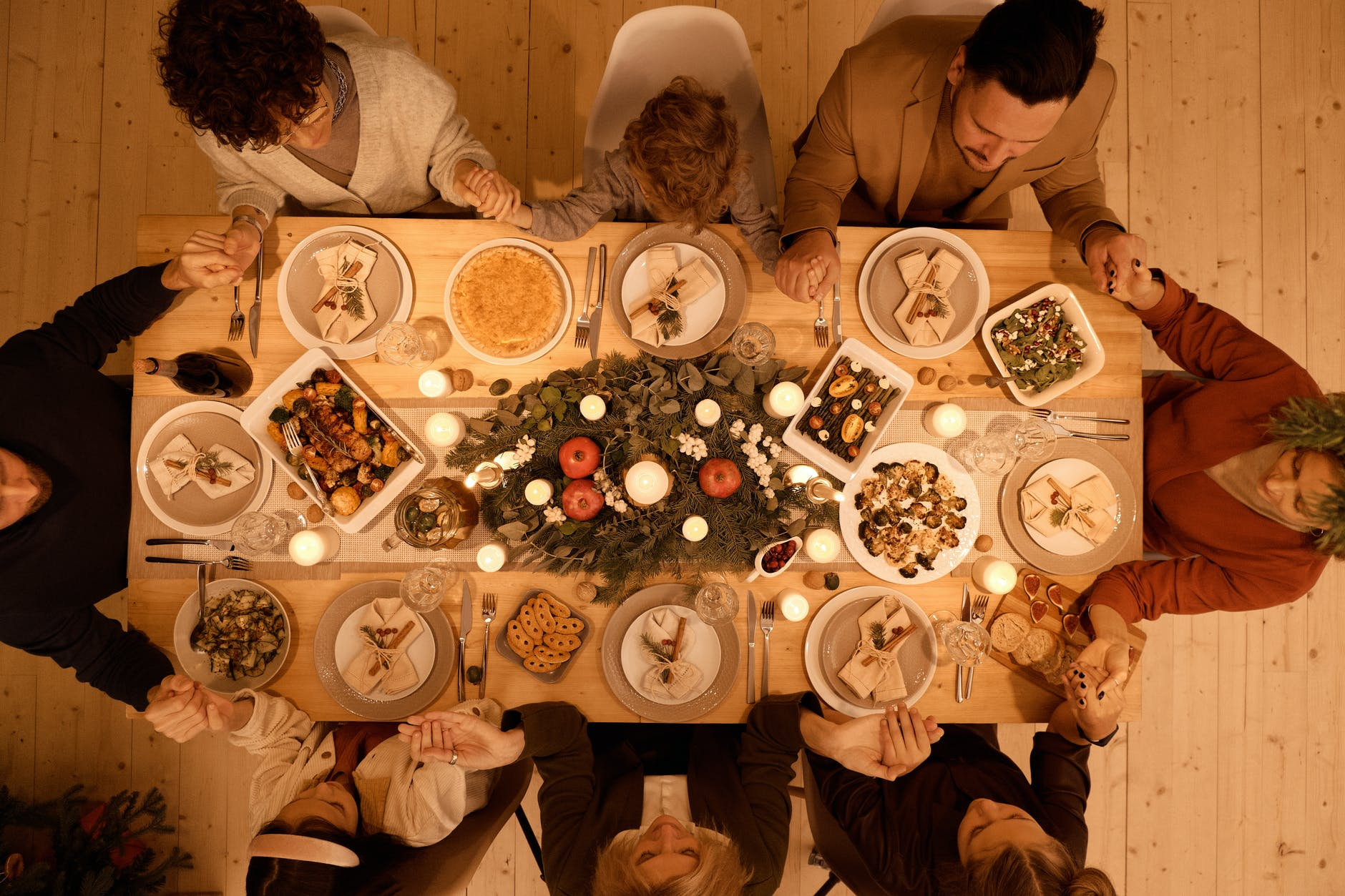 A group of people pray over dinner at a table full of food.